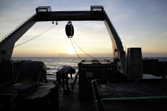 Colette Kelly of Stanford University stores seawater samples on deck in the twilight.