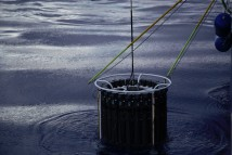 The trace metal clean CTD rosette emerges from a calm sea, with one tag line attached and the other reaching out for its loop of rope.