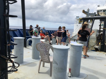 The GP15 team celebrates crossing the equator with music and dancing on the bow of the Roger Revelle.