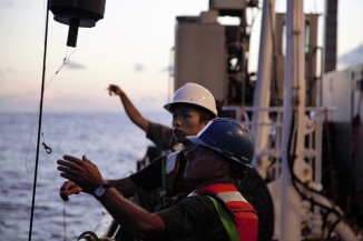 Members of the pump team Steven Pike (foreground) of WHOI and Yang Xiang of UCSC prepare to grab the winch cable to retrieve their equipment.