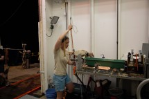 Zoe Sandwith of the WHOI sampling helium in the Roger Revelle's hangar. After filling a copper pipe with seawater she crimps it into individual sections that will be frozen for storage and transport.